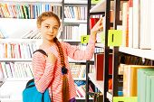 Girl with braid stands near bookshelf in library