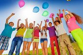 Children stand in semi-circle with balloons up