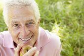 Senior man eating apple outdoors