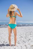 Slender woman in bikini on beach wearing sunhat on a sunny day