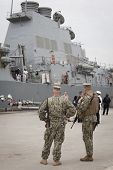 STATEN ISLAND, NY - MAY 21, 2014: Armed U.S. Navy personnel patrol Sullivans Piers while the guided-