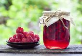 foto of jar jelly  - Raspberry preserve in glass jar and fresh raspberries on a plate - JPG