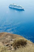 View Of The Blue Sea And The White Ship With The High Coast Of The Island Of Santorini