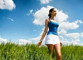 Low angle view of a beautiful elegant young woman in a green field of long grass standing looking into the distance with a dreamy expression under a blue sunny summer sky with fluffy white clouds