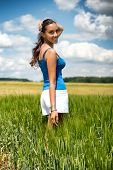 Beautiful young woman turning to smile at the camera as she stands in a scenic green field in the countryside