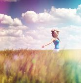 Woman frolicking in a summer field with colorful flare effect in rainbow or spectral colors under a