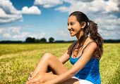 Tanned beautiful young woman in a recently cut green grassy farm field sitting sideways looking at t