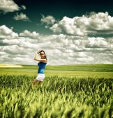 Pretty young girl in white summer shorts standing sideways in a green wheat field under a dramatic s