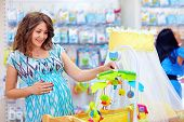 Pregnant Woman Buying Cradle With Mobile Toy For Baby