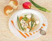 Plate soup on dish with striped napkin