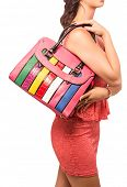 Woman wearing pink lace mini dress. With bright stripe candy fashion bag. Isolated on white studio b