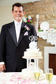 Handsome groom standing beside the wedding cake at his gay wedding, waiting for his husband.