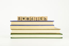 stock photo of dialect  - swedish word on wood stamps stack on books language and academic concept - JPG
