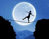 image of gap  - Young woman walking on rope above gap at night - JPG