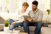 Happy young couple using tablet pc at home, sitting on sofa, smiling.  .