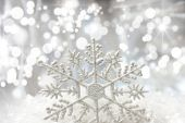 Christmas snowflake nestled in snow with bokeh lights