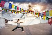 stock photo of nepali  - Woman doing yoga warrior pose at Bodnath stupa Kathmandu Nepal - JPG
