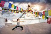 stock photo of virabhadrasana  - Woman doing yoga warrior pose at Bodnath stupa Kathmandu Nepal - JPG