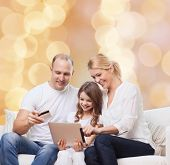 family, holidays, shopping, technology and people - smiling family with tablet pc computer and credit card over beige lights background
