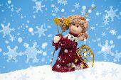 angel doll on snowdrift with snowflakes