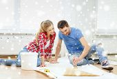 repair, building, teamwork and home concept - smiling couple smearing wallpaper with glue