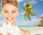 beauty, people, travel and health concept - beautiful young woman with bare shoulders over tropical beach background