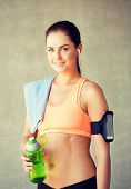 fitness, sport, training, drink and lifestyle concept - woman with bottle of water in gym