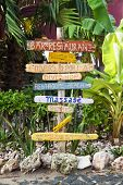Signpost made of flotsam at tropical resort showing directions to facilities at beach