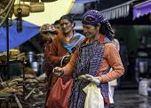 Women in traditional clothing walking in Manali old Market, people watching and buying.