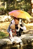 Mother with baby in the park under an umbrella