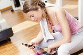 Smiling Woman With Smart Phone Resting From Workout At The Gym