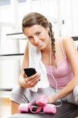 Smiling Woman Listening To Music At The Gym