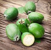 Three feijoa fruits with leaves on an old wooden table.