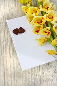 picture of gladiolus  - bouquet of beautiful yellow gladioluses chocolate hearts and a blank sheet of paper for inscription on the wooden background - JPG