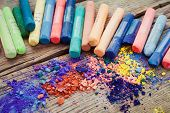 stock photo of pigment  - Collection of rainbow colored pastel crayons with pigment dust - JPG
