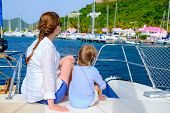 Back view of mother and daughter family sailing on a luxury yacht or catamaran boat
