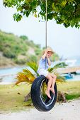 Adorable little girl having fun on tire swing on summer day