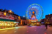 ALBA, ITALY - DECEMBER 30, 2013: Illuminated observation wheel and stall with sweets on town square as part of traditional Christmas and New Year celebrations.