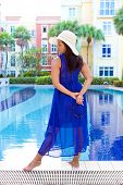 Beautiful hispanic woman in blue dress and sun hat standing by the edge of a swimming pool