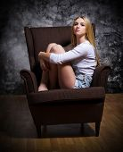Young girl sit in chair on rough grey wall background
