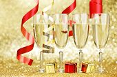 Glasses of champagne colorful ribbons on glitter background