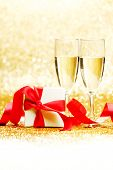 Champagne glasses and present in whitebox with red ribbon on golden background