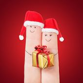 Fingers Faces In Santa Hats With Gift Box On Red Background. Celebrating Concept For Christmas Or Ne