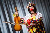 Funny clown plyaing violin against curtain
