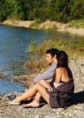 Ethnic Couple Sitting Outdoors On River Bank