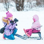 little girl photographed her sister sitting on a sled in the winter park