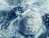 Christmas decoration. Christmas ball, pine cones, glittery jewels on white satin.