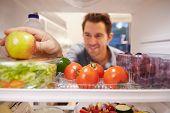 Man Looking Inside Fridge Full Of Food And Choosing Apple