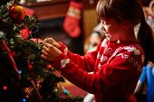 Little girl decorating Christmas tree with toys