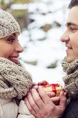 Young amorous couple with small present looking at one another outdoors